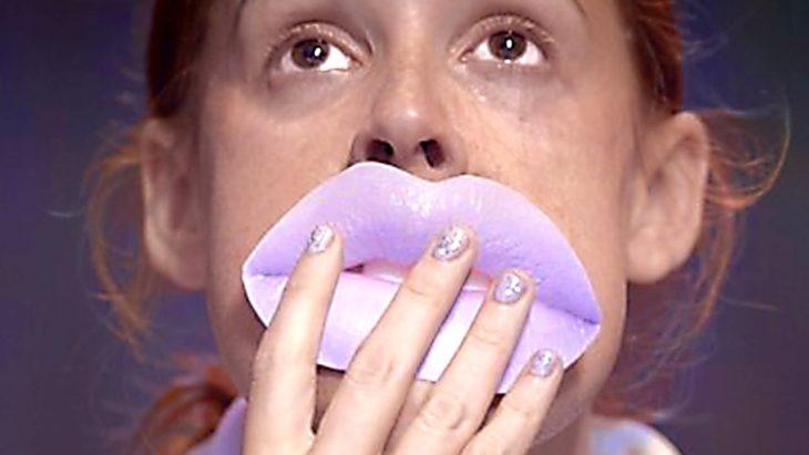 Chica cubriendo sus labios con una trozo de papel lila, escena de la película Pieles