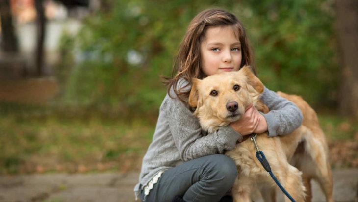 Niña pequeña de ojos verdes abrazando a su perro en un parque