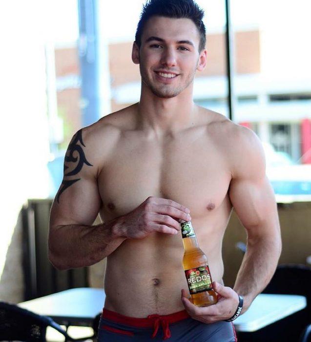 Mesero sosteniendo una cerveza en su mano mientras sonríe y posa para una foto