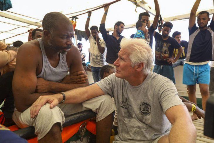 Richard Gere sentado apoya su mano en un migrante rescatado en el Mediterráneo