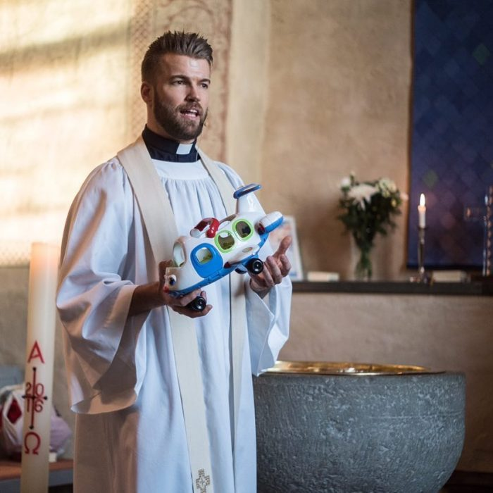 Sacerdote llamado Oskar dando una misa y sosteniendo un avión en sus manos