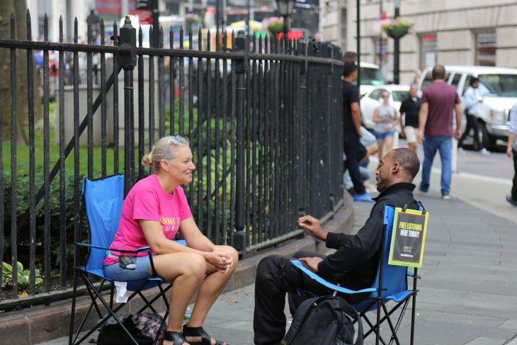 Una voluntaria de Sidewalk talk sentada en una silla colocada en una banqueta escucha a un joven sentado frente a ella