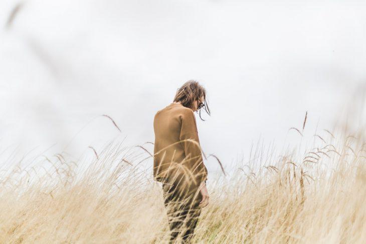 Mujer sola cabello corto en paisaje de pastizal