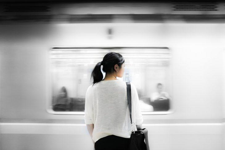 Mujer sola de espaldas en estación de metro