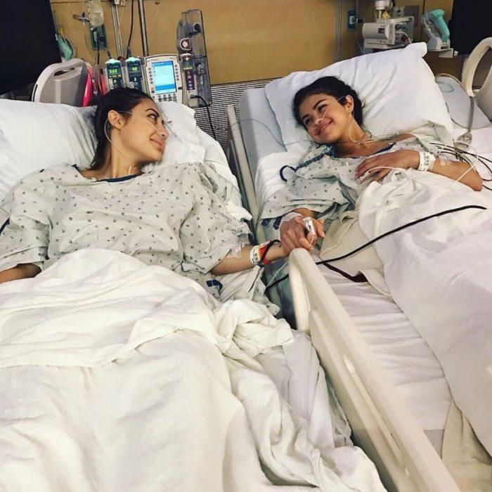 Selena Gomez y Francia Raisa recostadas en camillas de hospital y sujetadas de las manos