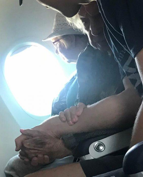 Chico sosteniendo la mano de una abuelita de 96 años en pleno vuelo