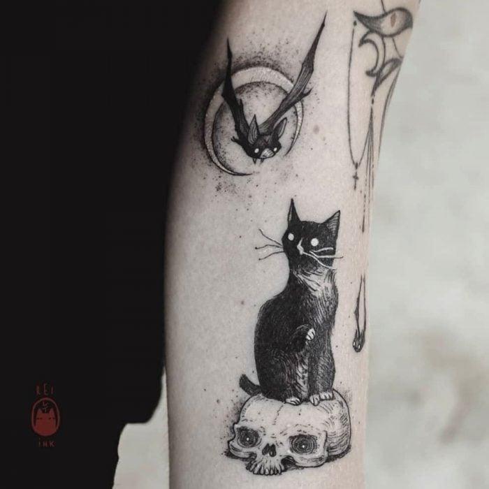 Tatuaje de halloween, gato negro sobre un cráneo mirando a un murciélago en la luna