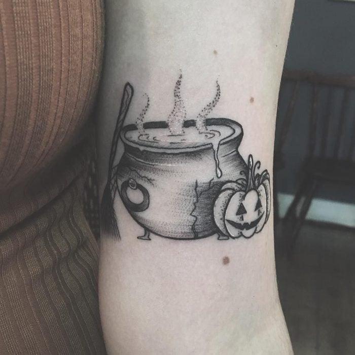 Tatuaje de halloween, caldero de bruja con calabaza y escoba en estilo minimalista en blanco y negro