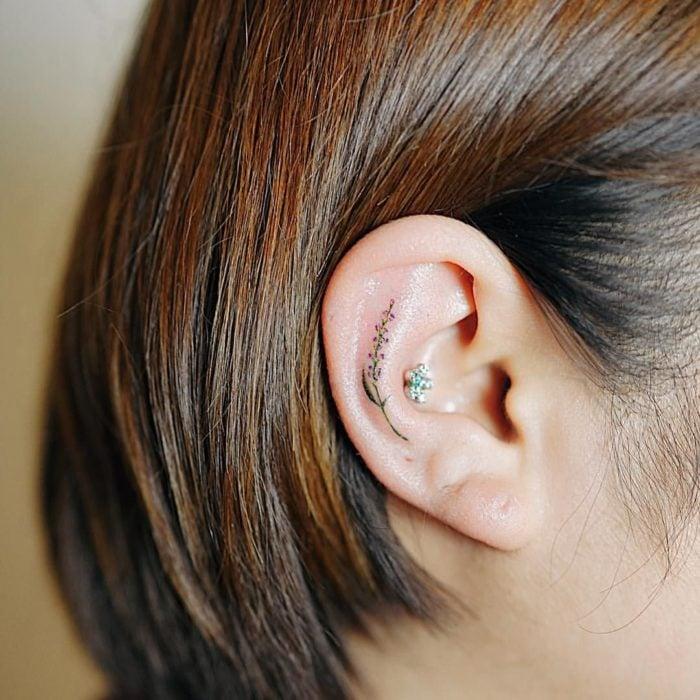 Chica con un tatuaje en la oreja en forma de flores de colores