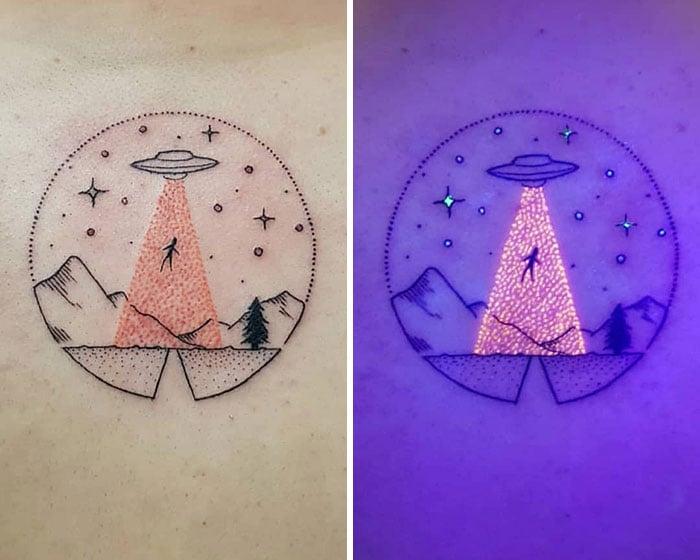 Tatuaje con un circulo lleno de estrellas, silueta d emontañas y un platillo volador en abducción con efecto ultravioleta