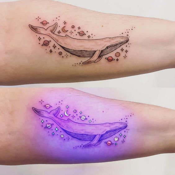 Tatuaje de la silueta d euna ballena con planetas alrededor con efecto ultravioleta