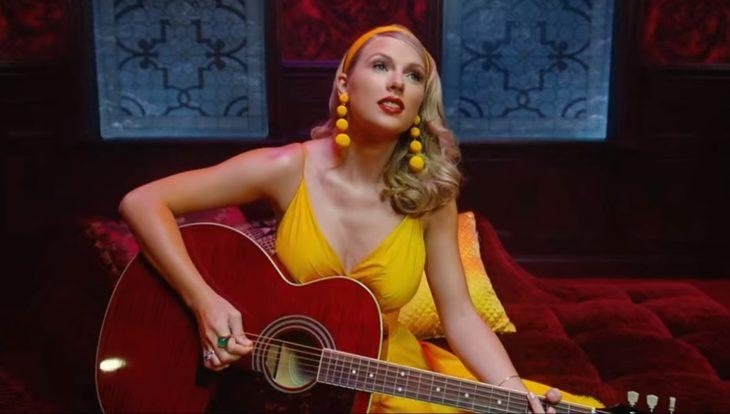 Escena del video Lover de Taylor Swift, está tocando la guitarra sentada en un sillón rojo oscuro y con vestido amarillo y aretes amarillos largos