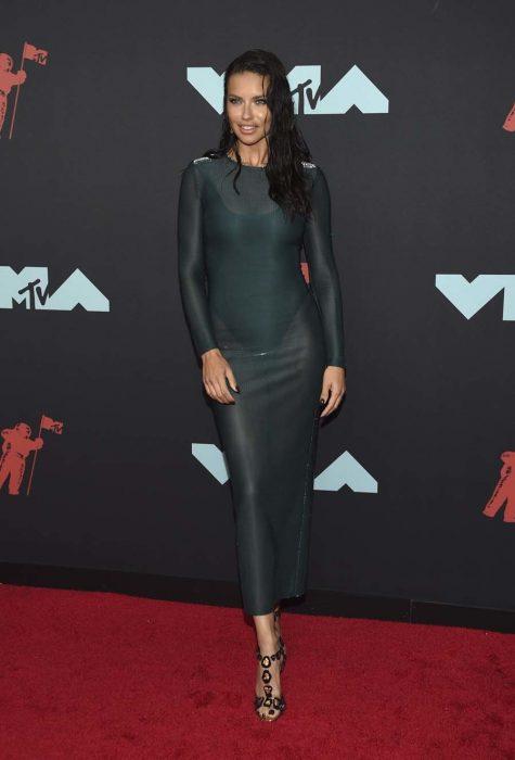 Adriana Lima usando un vestido verde con transparencias y un body de color negro en la alfombra roja de los premios MTV music awards 2019