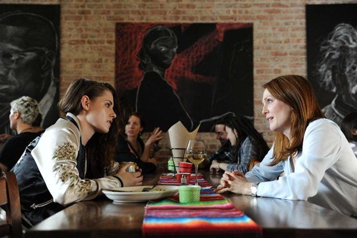 madre e hija están de frente en una mesa de restaurante que tiene un camino de mesa colorido