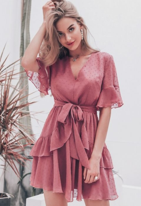 Chica rubia con vestido eestilo playero, rosa con lunares y olanes