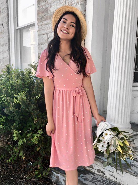 Chica con vestido rosa de puntos blancos, con sombrero y un ramo de flores