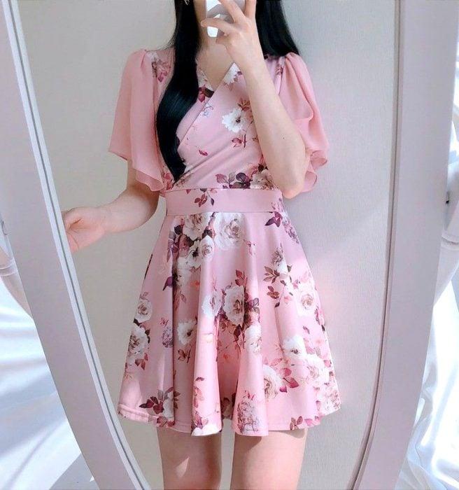 Chica tomándose selfie en el espejo, con vestido rosa, corto, floreado