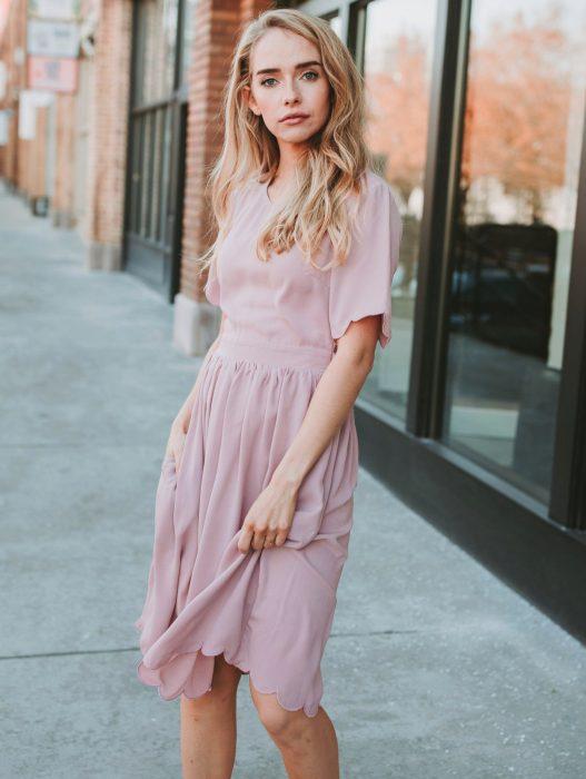 Chica rubia de ojos azules con vestido sencillo de color rosa