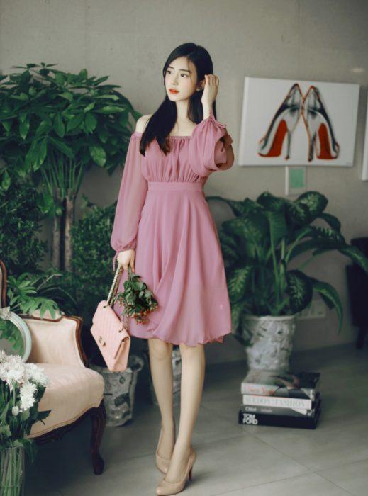 Chica coreana de cabello negro y lacio, con vestido rosa sin hombros, estilo campesino de gasa