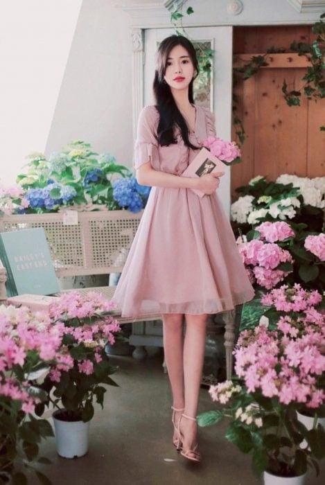 Chjca coreana con vestido rosa de gasa, rodeada de flores rosas y azules, con un libro en la mano