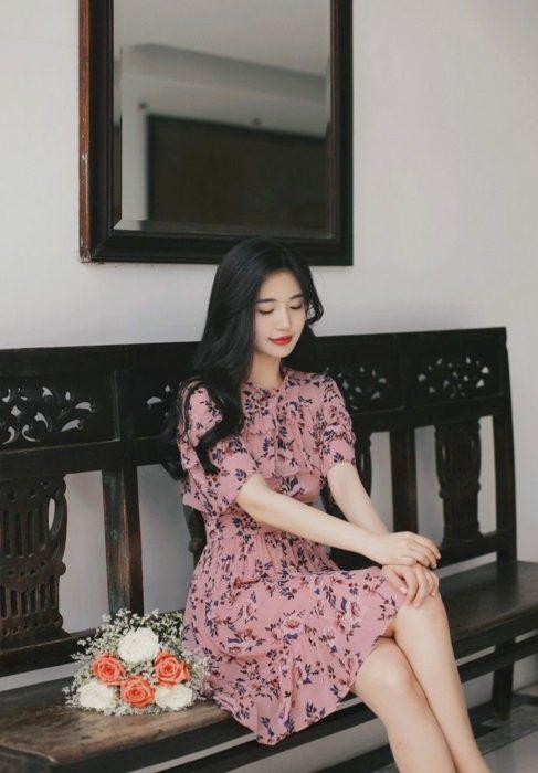 Chica coreana de cabello negro y ondulado, con vestido floreado a la rodilla, sentada en una banda y con un ramo de flores