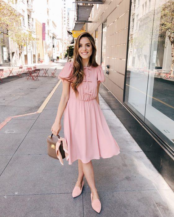 Chica sonriendo en la calle, con cabello castaño peinado hacia un lado, con vestido rosa casual