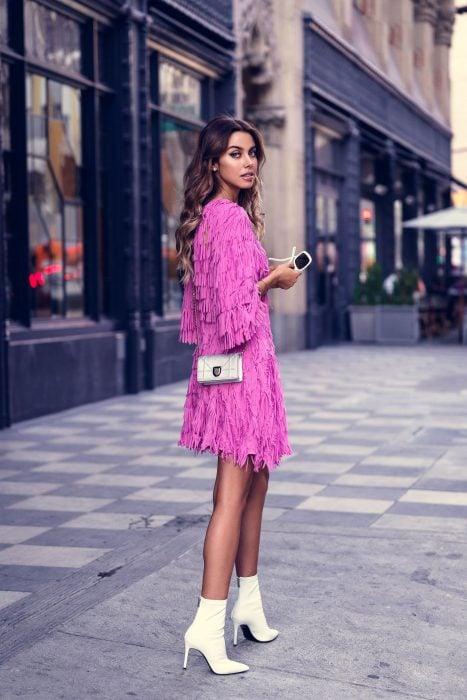 Chica con vestido rosa de flecos arriba de la rodilla