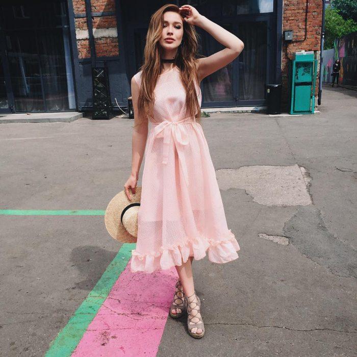 Chica en la calle, cabello largo castaño y con volumen, con vestido sin mangas, rosa, con listón en la cintura y con sombrero de playa