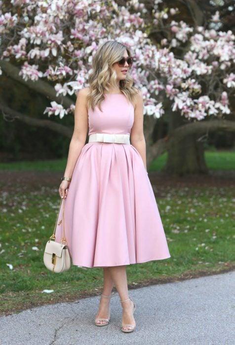 Chica rubia con lentes de sol y vestido rosa liso sin mangas, frente a un árbol floreado