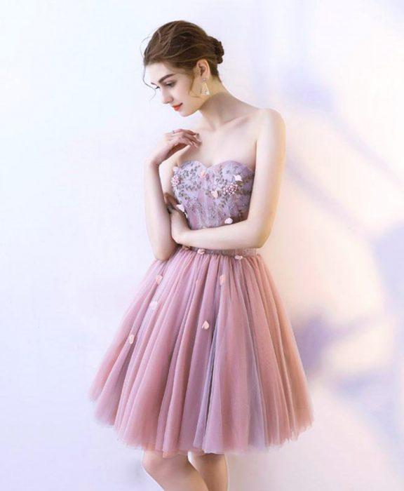 Mujer con vestido de fiesta sin mangas ni tirantes, con flores pegadas en el corsette