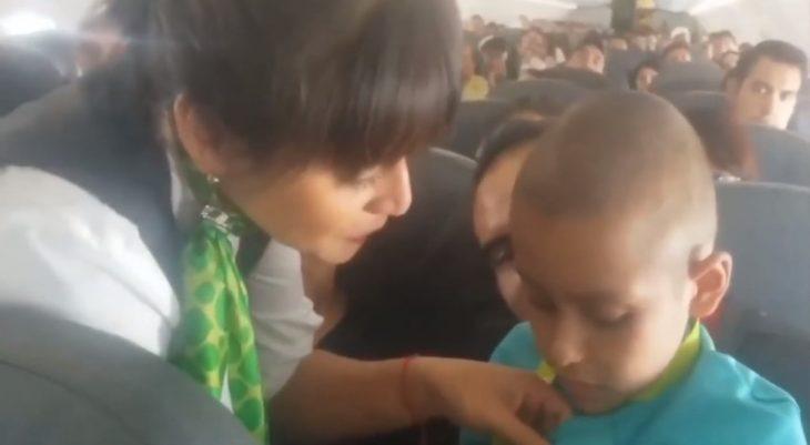 Azafata Cynthia Borges poniendo su insignia a Jonathan durante el vuelo a Mazatlan