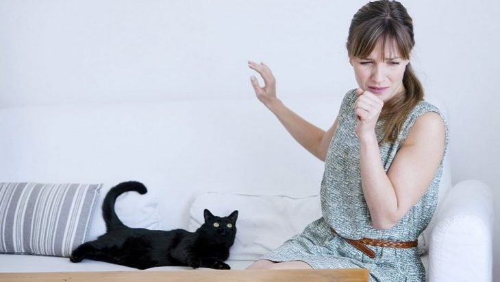 Mujer estornudando porque tiene a un gato negro al lado