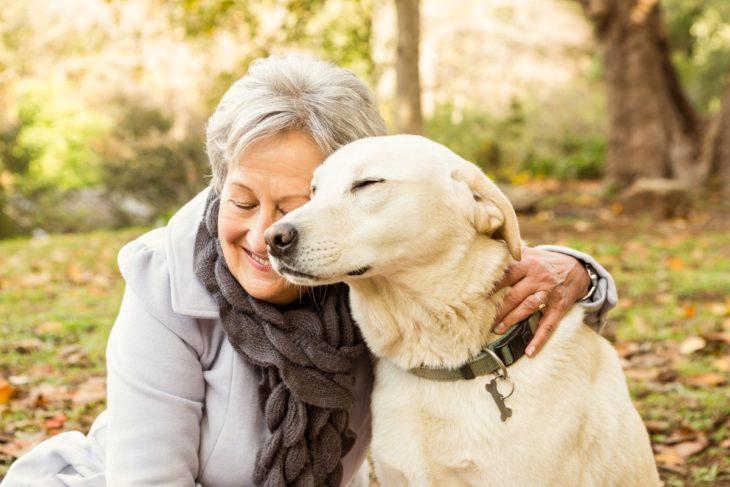 Mujer adulta mayor abrazando amorosamente a su perro