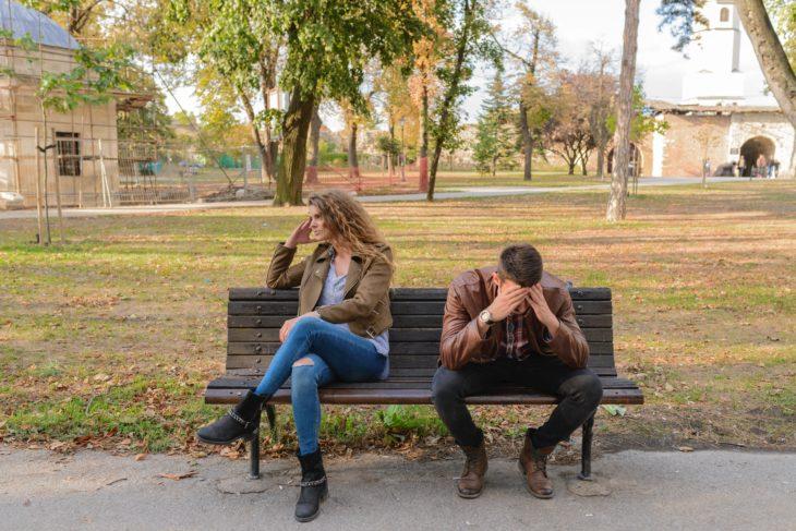 L'uomo si aggrappò al viso e la donna si girò, entrambi seduti su una panchina del parco