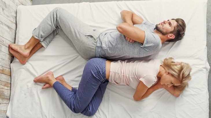 Uomo arrabbiato e donna sdraiata a letto