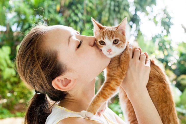 Mujer besando a su gato