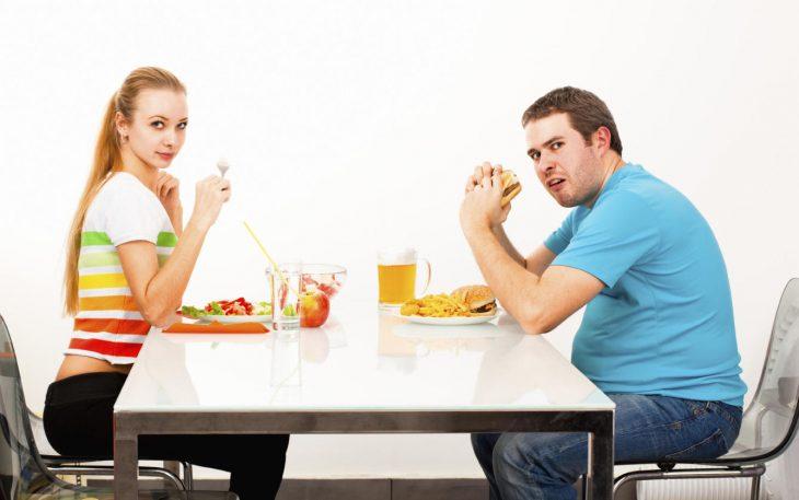Mujer delgada comiendo saludable y hombre gordito comiendo hamburguesa y papas