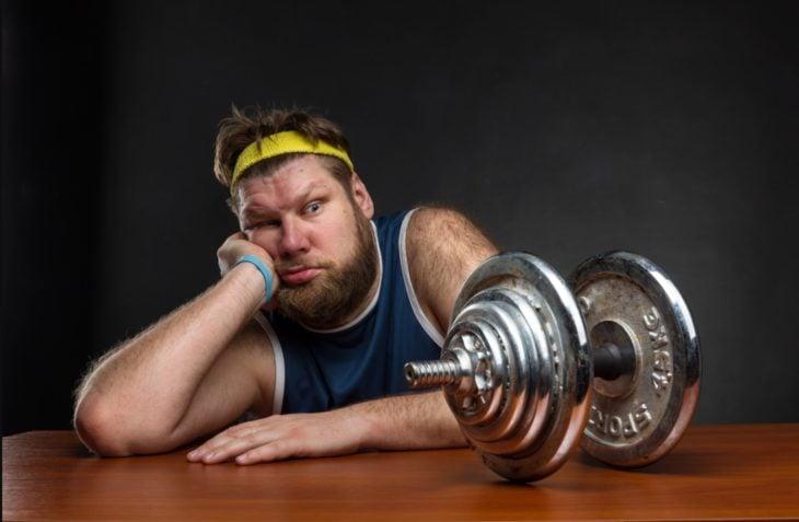 Hombre gordo viendo una pesa de gimnasio