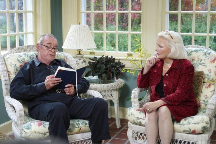 Una pareja de la tercera edad sentados en una sala de rattan, por la ventana se observa un jardín, el señor está leyendo y la señora lo observa con atención