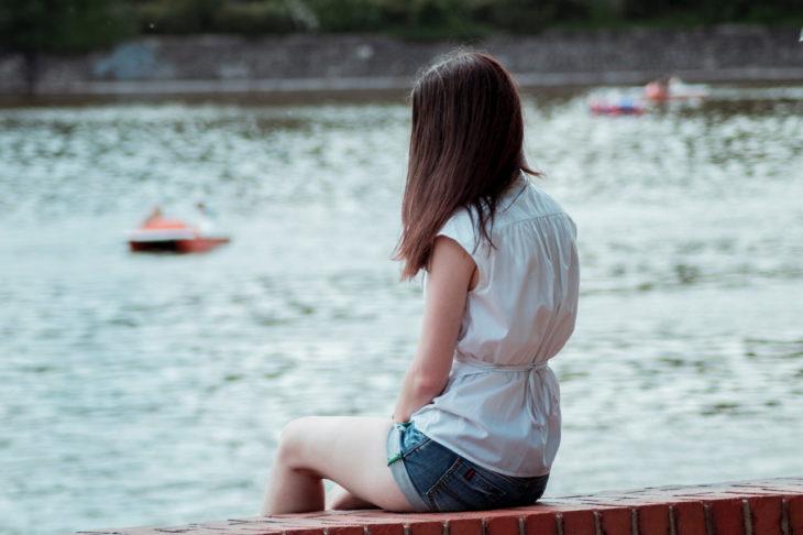 una mujer sentada a la orilla de un lago, sola, con blusa blanca, de espaldas