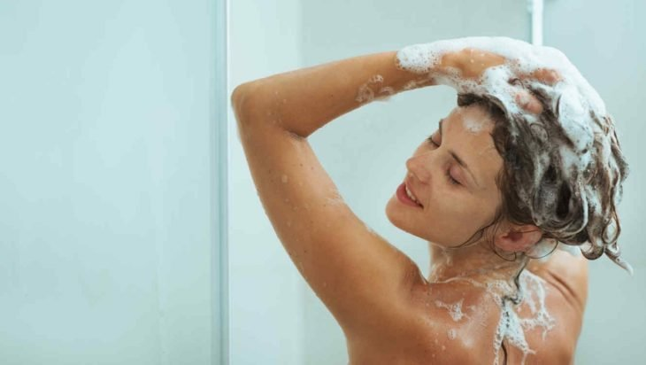 Mujer en la regadera lavándose el cabello