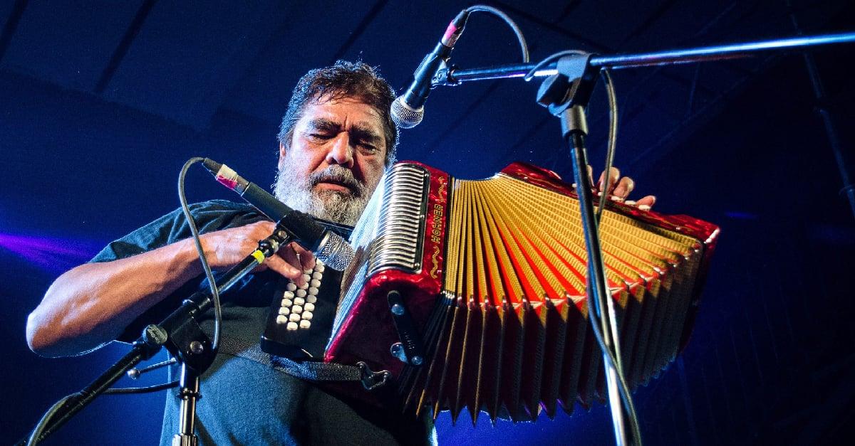 Celso Piña tocando acordeón en un escenario