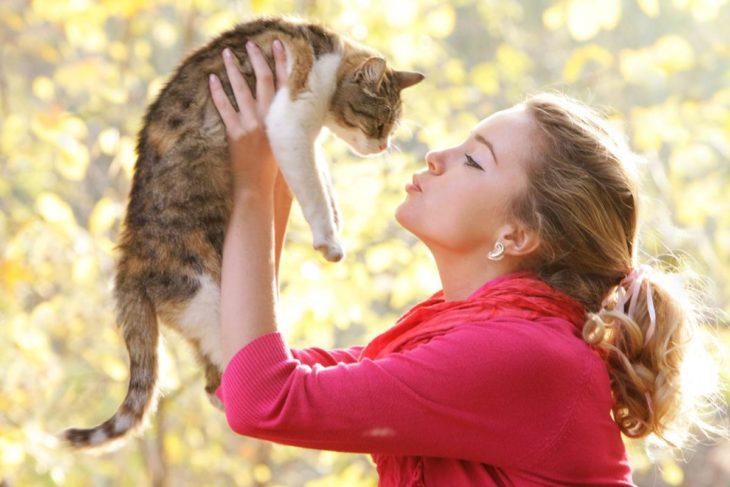 Mujer cargando a su gato y simulando que le dará un beso