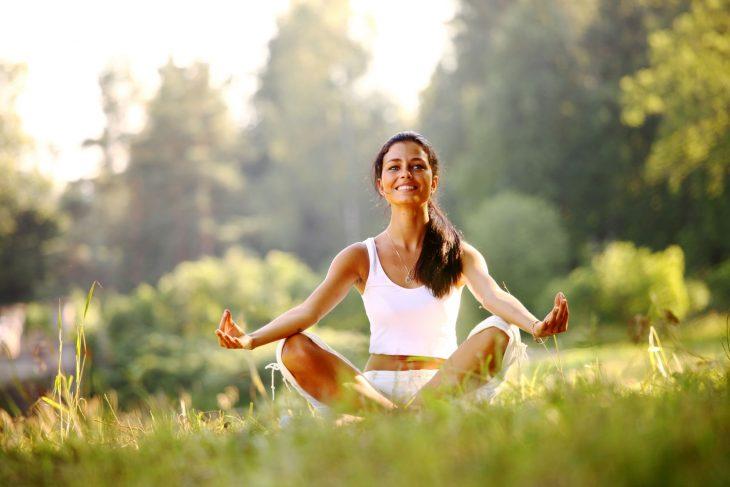 Mujer meditando en un campo