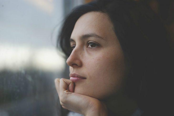 Mujer pensando frente a la ventana