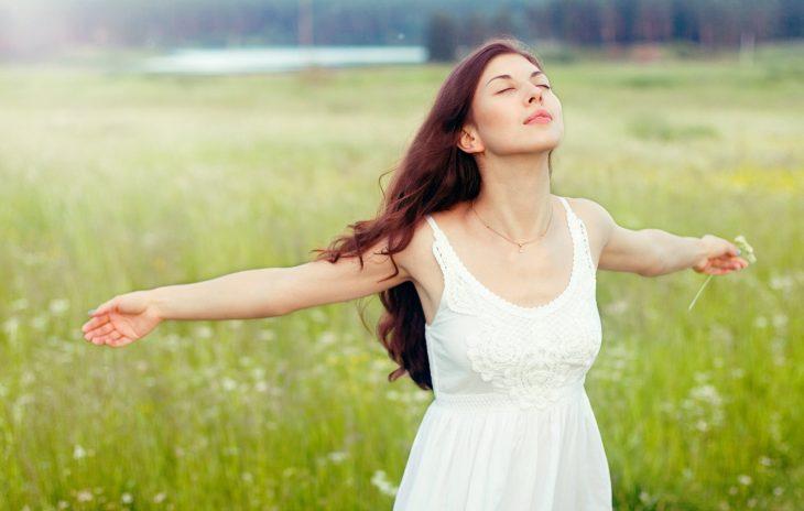 Mujer abriendo sus brazos y respirando profundamente