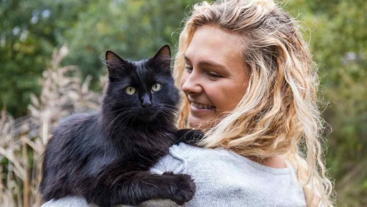 Mujer rubia cargando a un gato negro