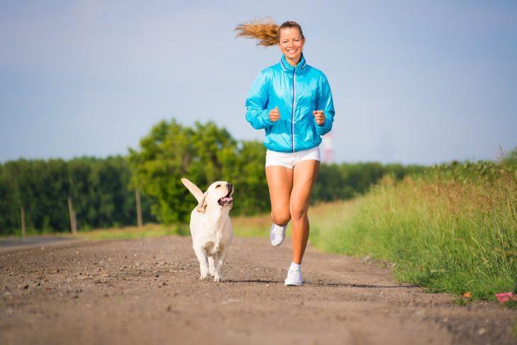 Mujer con ropa deportista corriendo junto a su perro por un campo