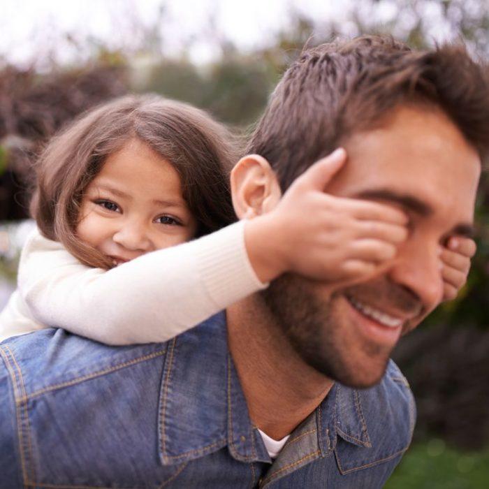 Niña tapándole los ojos a su papá, ambos sonriendo