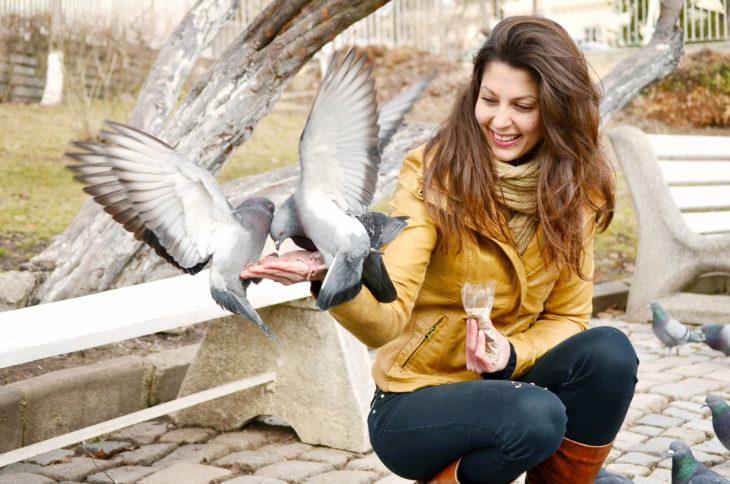 Mujer alimentando a las palomas